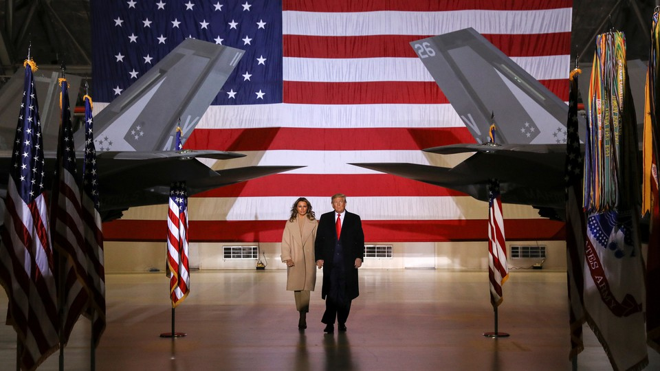 Donald and Melania Trump at Joint Base Andrews. They are flanked by Air Force planes on their left and right.