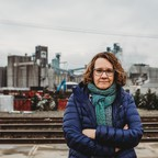 A photo of activist Linda Garcia standing in front of train tracks and an industrial facility.