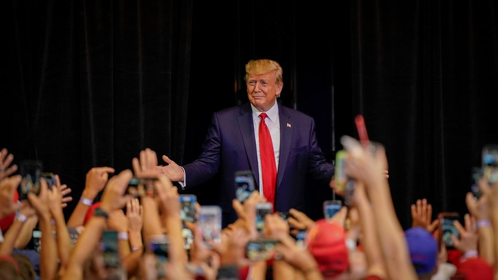 Donald Trump stands in front of supporters at a campaign rally.