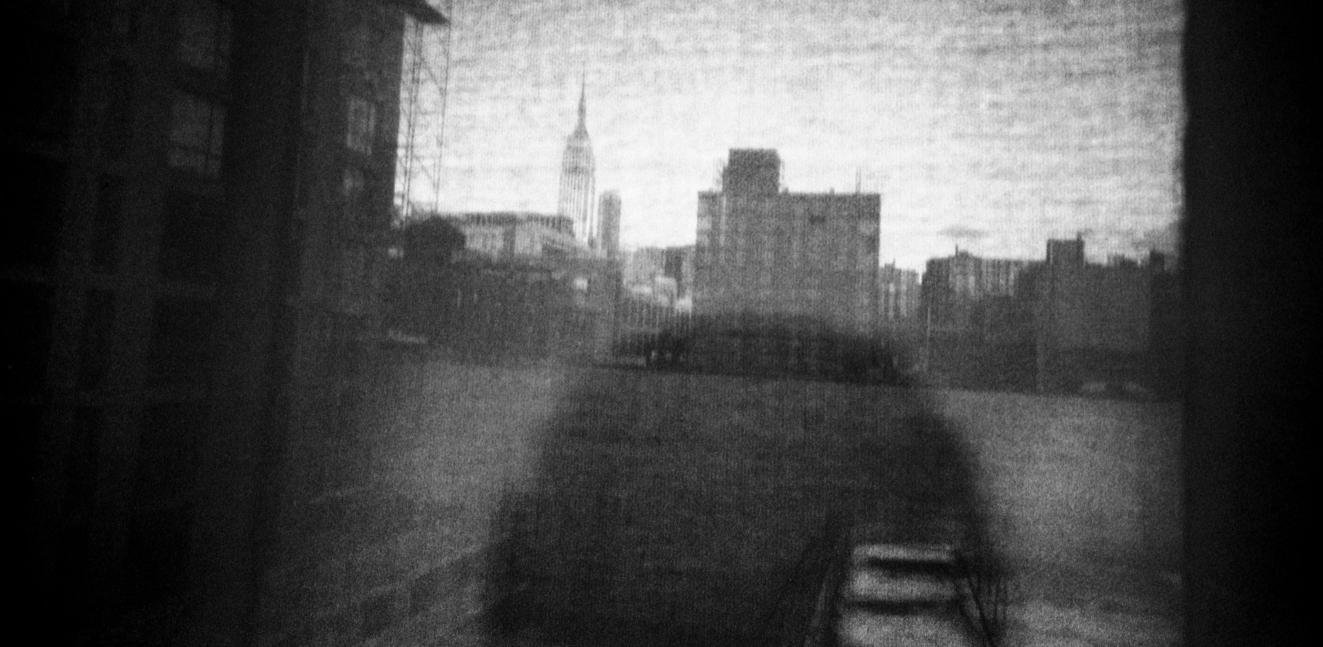 Shadow figure looking over black-and-white city scene