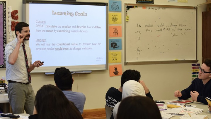 """A teacher stands near a whiteboard that describes """"Learning Goals"""" and another board with math problems; students sit at desks."""