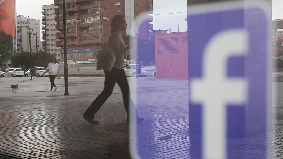 People walk past a Facebook logo on a shop window