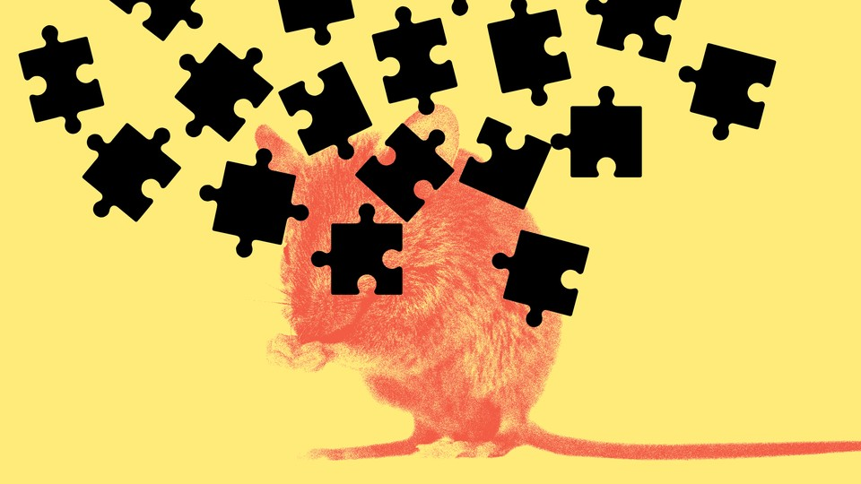 A red mouse on a yellow background with black puzzle pieces raining down