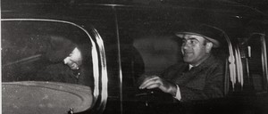 Two men sit in a car at night