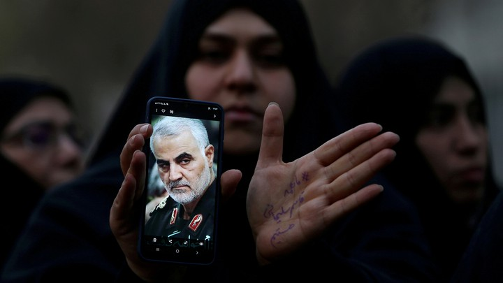 An Iranian woman displays an image of Qassem Soleimani on her phone.