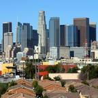 The Los Angeles skyline looms above single-family homes.