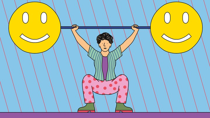 A person lifts a large barbell with smiley faces on either end.