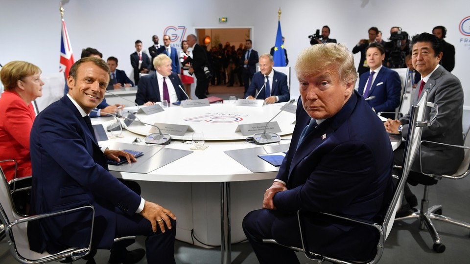 Donald Trump sits with the other G7 summit attendees at a round table.