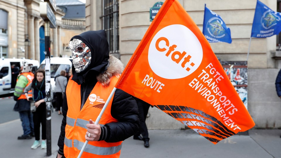 A masked demonstrator holds a flag of the French Democratic Confederation of Labour union (CFDT) in Paris during a national protestagainst the government's labour reforms on September 18, 2017.