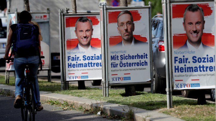 A cyclist passes posters featuring the far-right Freedom Party leader, Norbert Hofer, and former Interior Minister Herbert Kickl in Vienna.