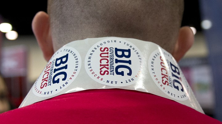 "The back of someone wearing stickers that say ""Big Government Sucks"" around their neck"