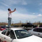 A man in Puerto Rico tries to get cell phone service from a mobile phone antenna.