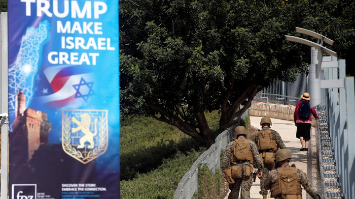 Military personnel patrol next to a sign welcoming the move of the U.S. embassy to Jerusalem.
