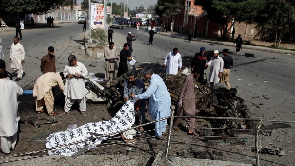 Police and rescue officials cover a body after a blast in Quetta, Pakistan on June 23, 2017.