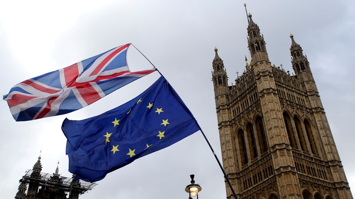 A British flag flies atop an EU flag outside the British Parliament.