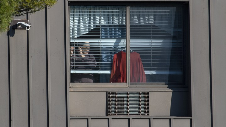A resident looks through a window at a New Jersey nursing home.