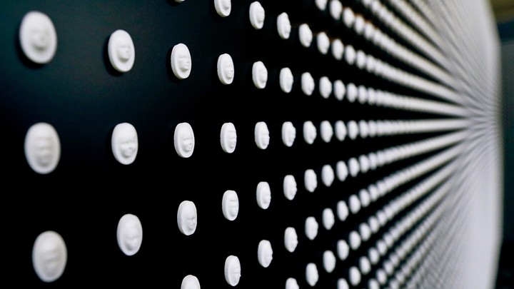 A black wall displays flat white pills with faces carved into them.
