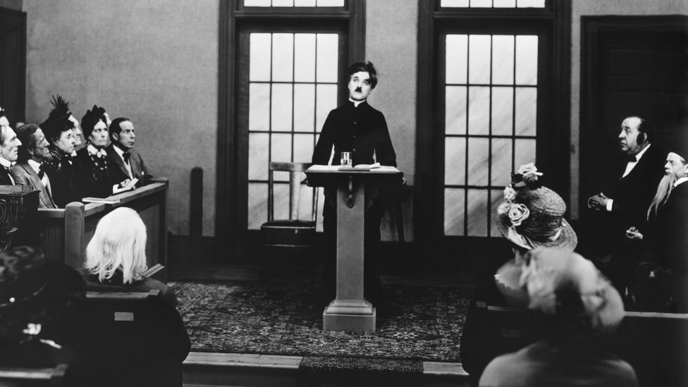 A black-and-white photo of Charlie Chaplin at a podium, surrounded by onlookers in pews