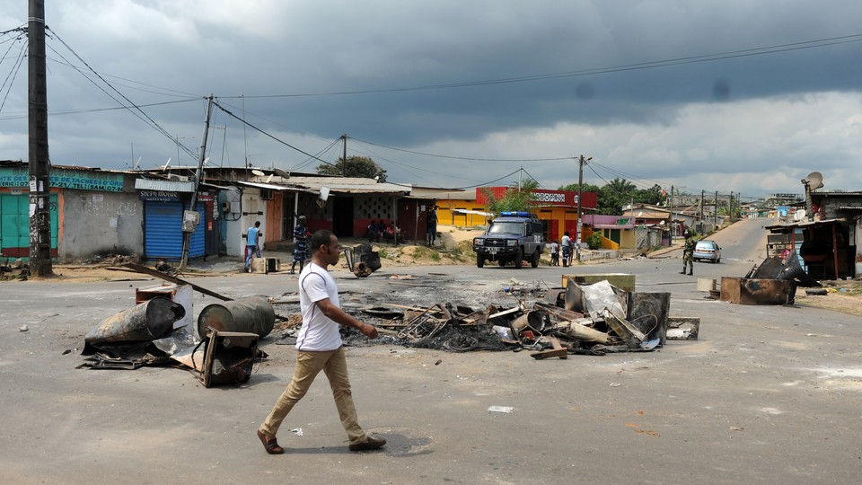 A man walks past remnants from election protests in Libreville, Gabon.