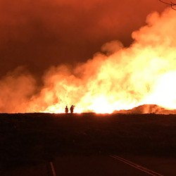 A red sky and yellow-lit smoke background USGS scientists working in front of the actively outgassing Fissure 8 vent, in Hawaii.