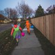 A girl and a boy in Halloween costumes run down an empty sidewalk