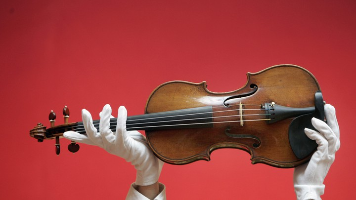 A person wearing white gloves holds up a violin