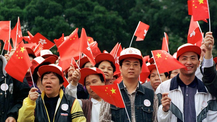 A large group of people wave Chinese flags.
