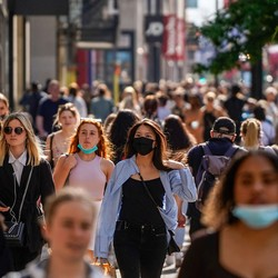 People walking outside, some with masks on and some without