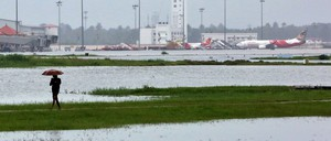 A person walks with floods and grounded airplanes in the background.