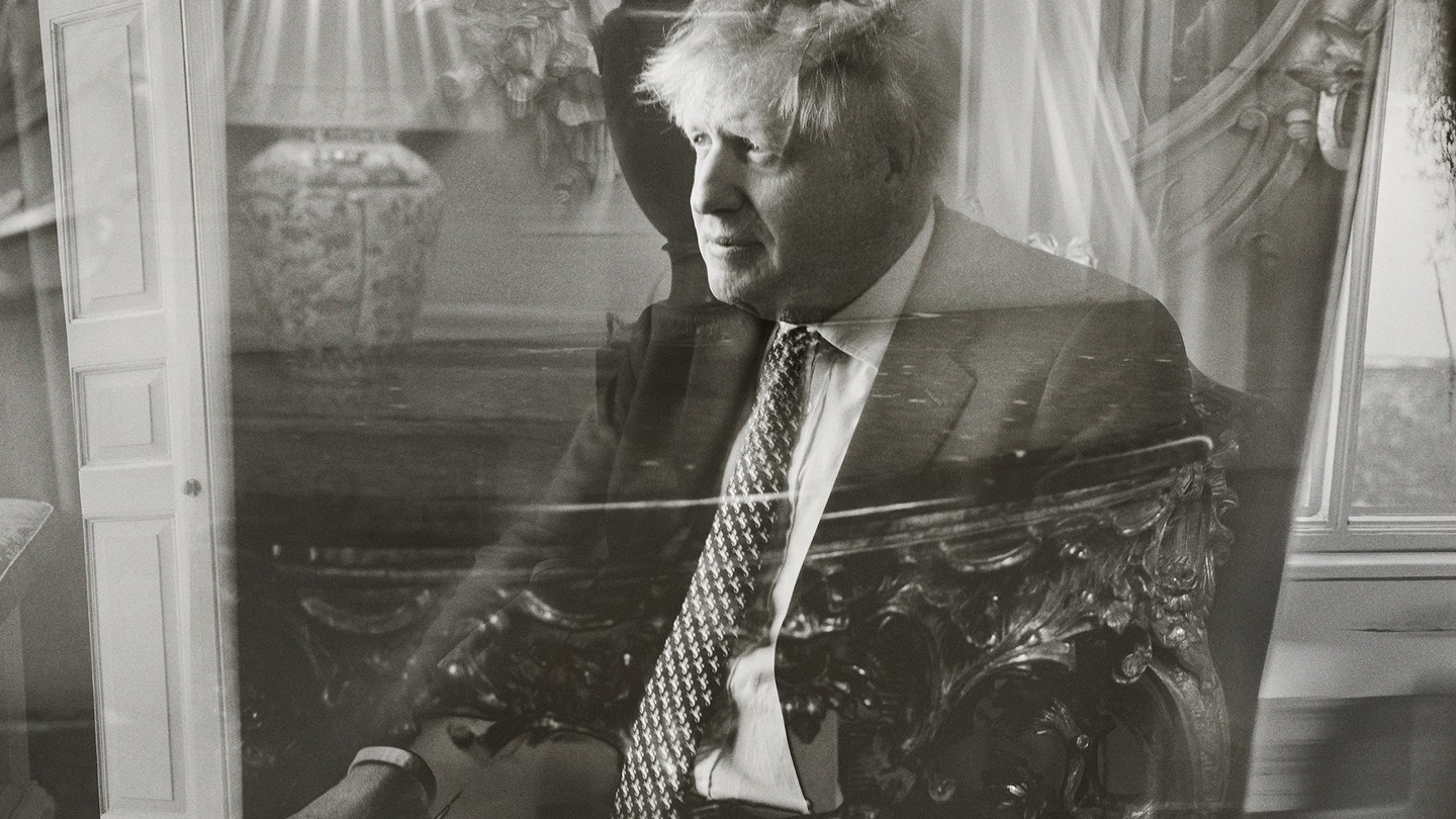 Photo: Prime Minister Boris Johnson seated, with superimposed reflection through glass, 10 Downing Street, May 2021