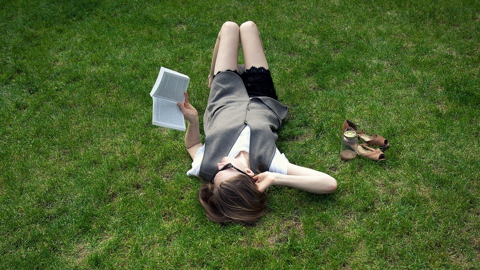 Woman reading a book in a field