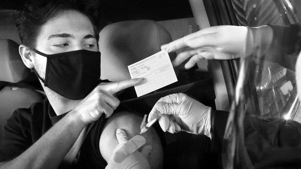 A person getting vaccinated with their vaccination card.
