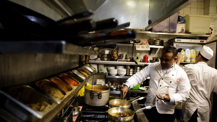 "The owner of a London ""curry house"" cooks a meal."
