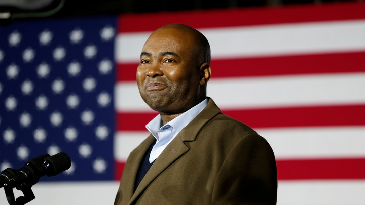 Jaime Harrison in front of an American flag