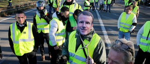 """A man wears a mask with the likeness of French president Emmanuel Macron as people take part in the nationwide """"Yellow Vest"""" demonstrations, a symbol of a French drivers' protest against higher fuel prices, in Haulchin, France."""