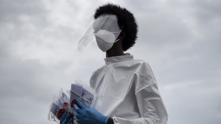 A health-care worker holding coronavirus tests