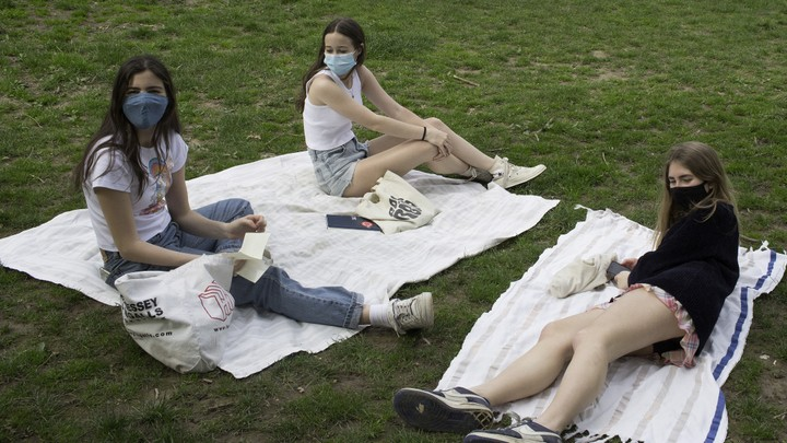 Three teenagers wearing masks sit apart on picnic blankets.