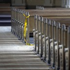 A row of empty pews in an abandoned church.