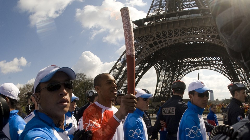 A French athlete, surrounded by Chinese security officers, carries the Olympic torch in Paris in April 2008.