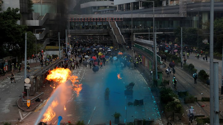 Riot police spray blue-colored water during a protest on China's National Day in Hong Kong.