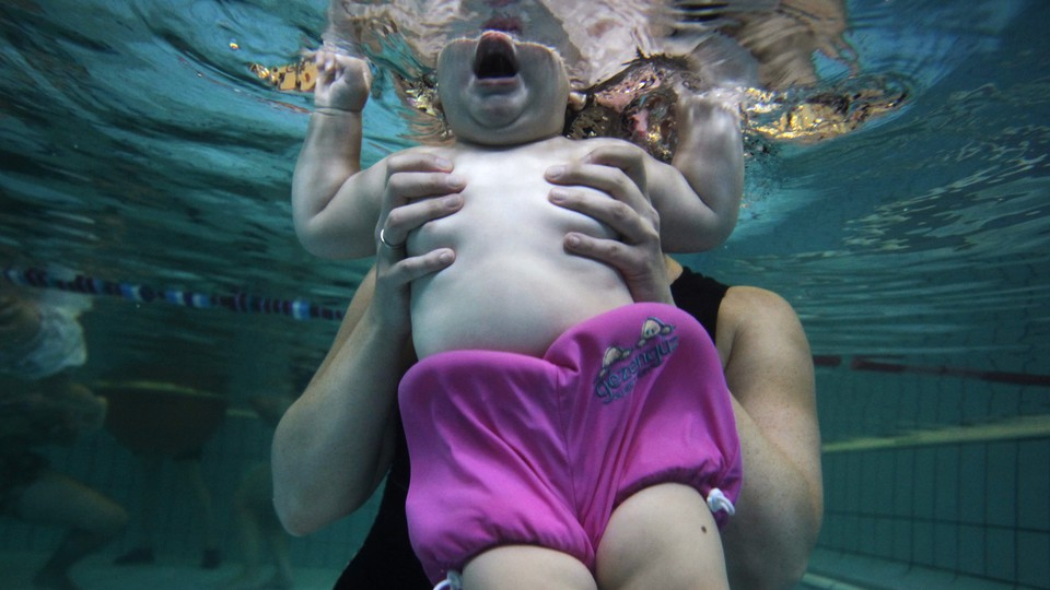 A baby is seen underwater from the chin down, held in the hands of an adult.