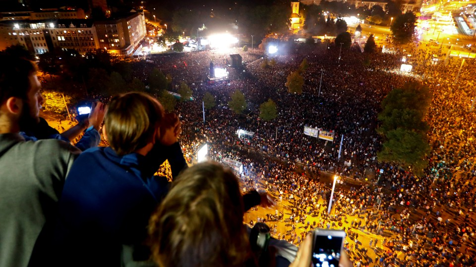 People photograph a crowd of concert-goers below