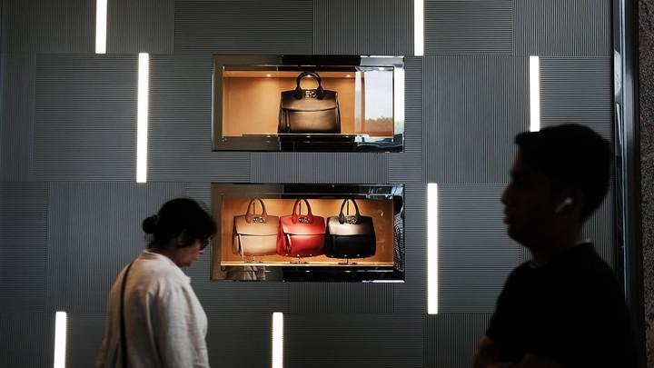 People walk in front of a display of handbags