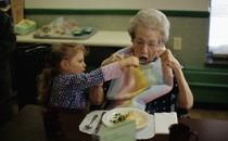 A toddler feeding an elderly woman from a fork.