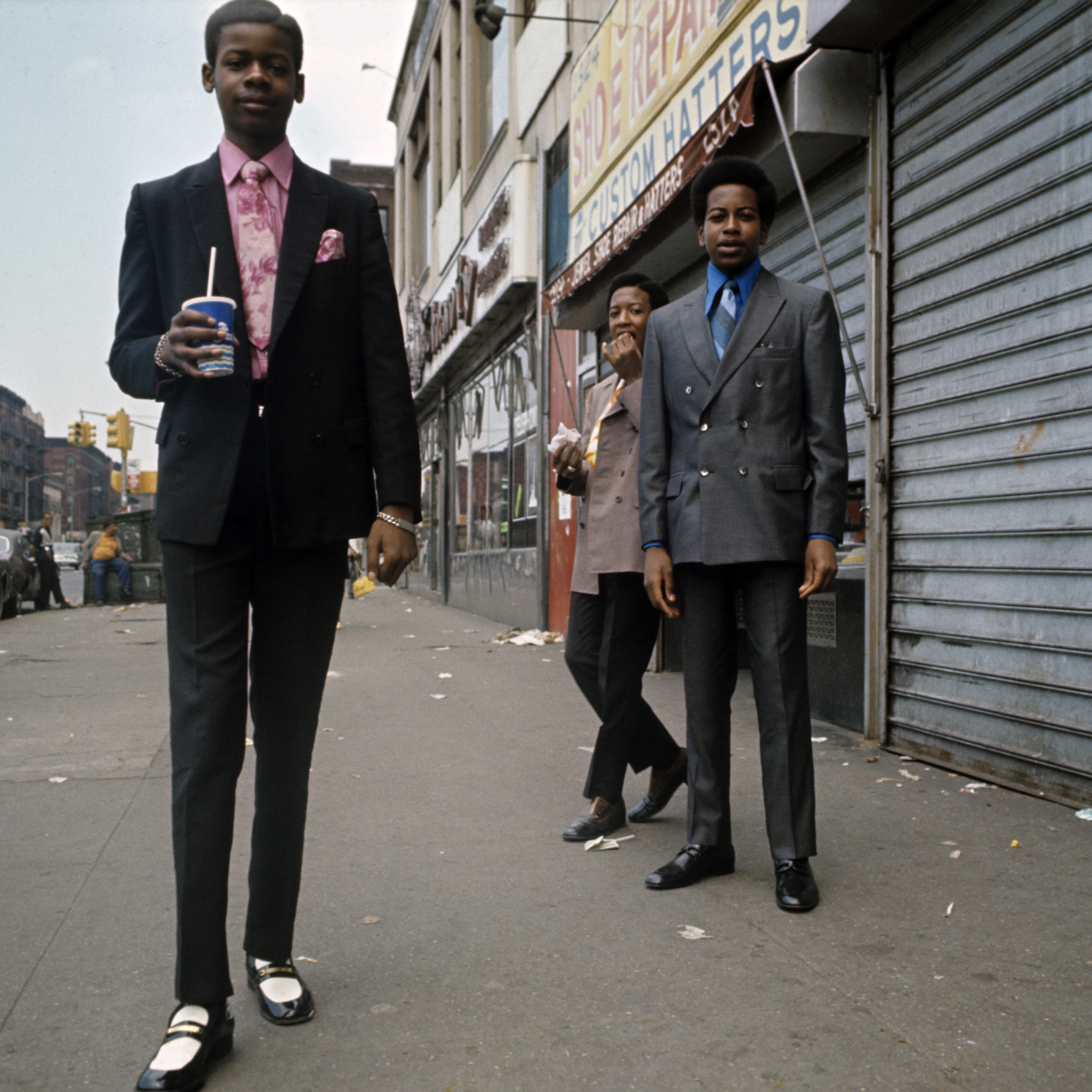 a teen boy dressed in a suit on a street the boys behind him