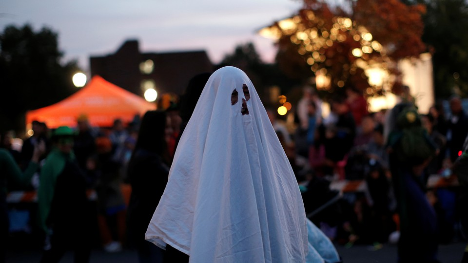 A man in a ghost costume marches in the annual Nyack Halloween Parade, in October 2016.
