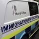 """A British government Home Office van is seen with the words """"immigration enforcement"""" along its side."""