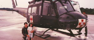 A mother and small child stand in front of a helicopter