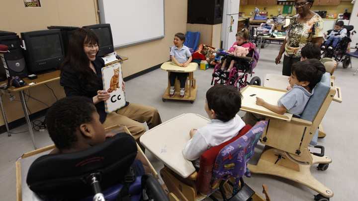 """A woman holds a board with a cat drawing and the letter """"C."""" A semicircle of students with disabilities surrounds her"""