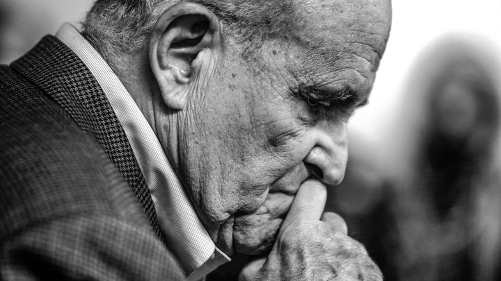 Rudy Giuliani looking at his clasped hands.